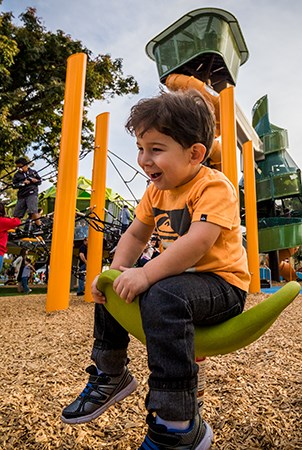 A boy smiling while sitting on a playground Saddle seat spinner.