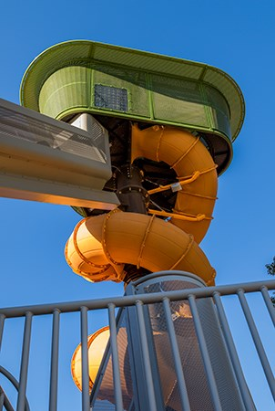 Ground level view up to the top of the palm tree playground structure and spiraling tubular slide.