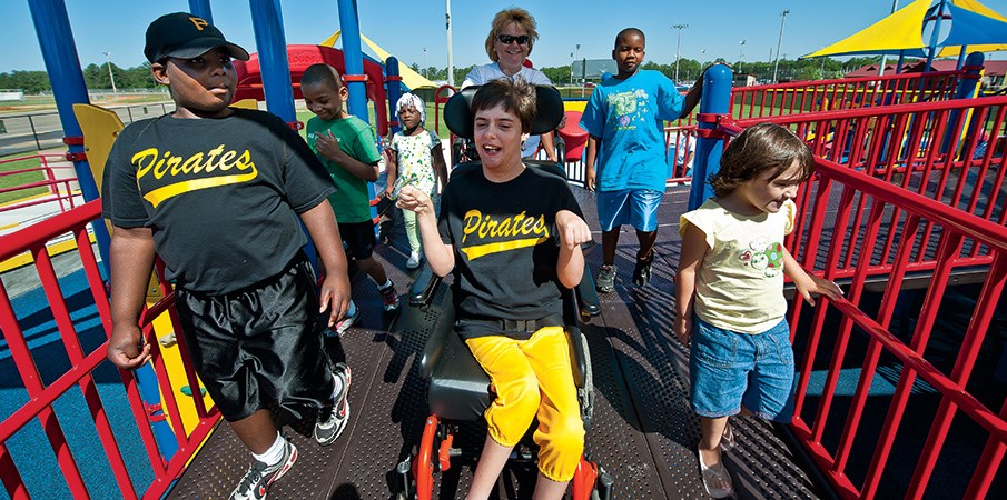 Boy smiling in wheelchair while wheeling down a inclusive PlayBooster playground decking with a group of children.
