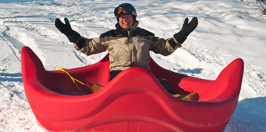 Landscape Structures founder Steve King sliding down a snowy hill on a OmniSpin playground spinner seat.