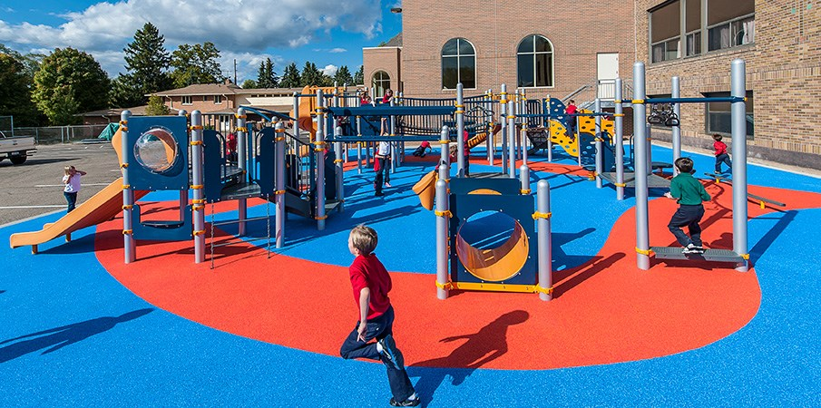 Full side view of a PlayBooster playground with PebbleFlex safety surfacing.
