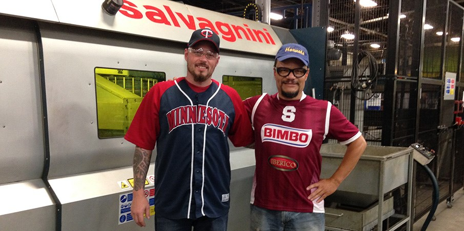 Two Landscape Structures employees smile for the camera while standing in front of a large manufacturing machine wearing team jerseys for Team Spirit Day.