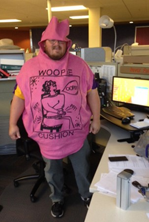 Landscape Structures Trevor Ryks poses for the camera at his cubical wearing a woopy cushion Halloween costume.